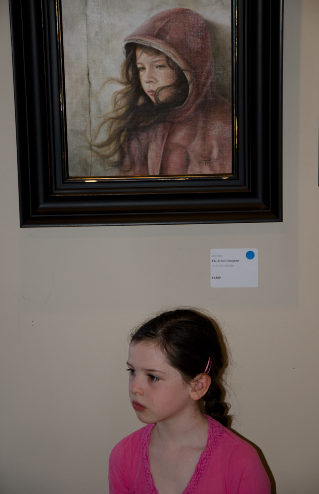 Grace poses under a portrait of herself