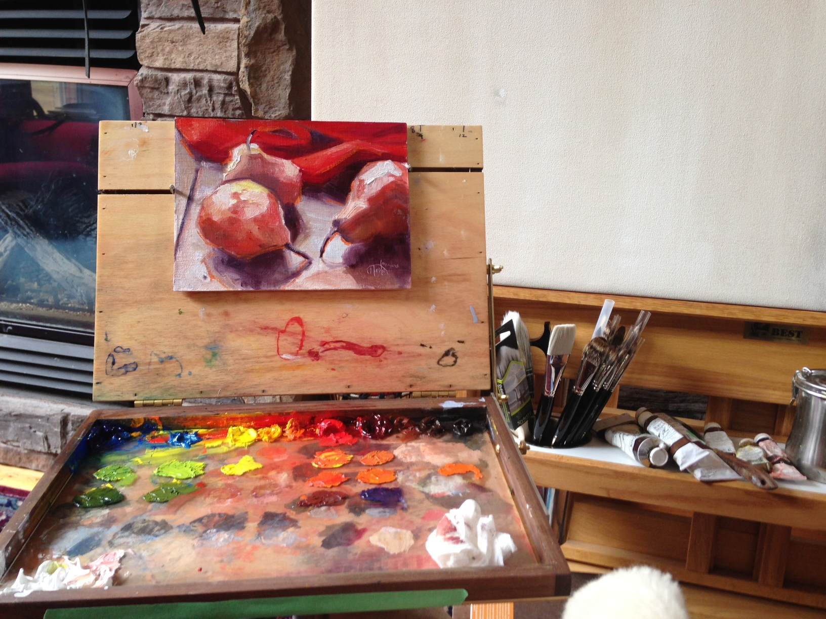 Janice Tanton's small painting setup beside the fire.