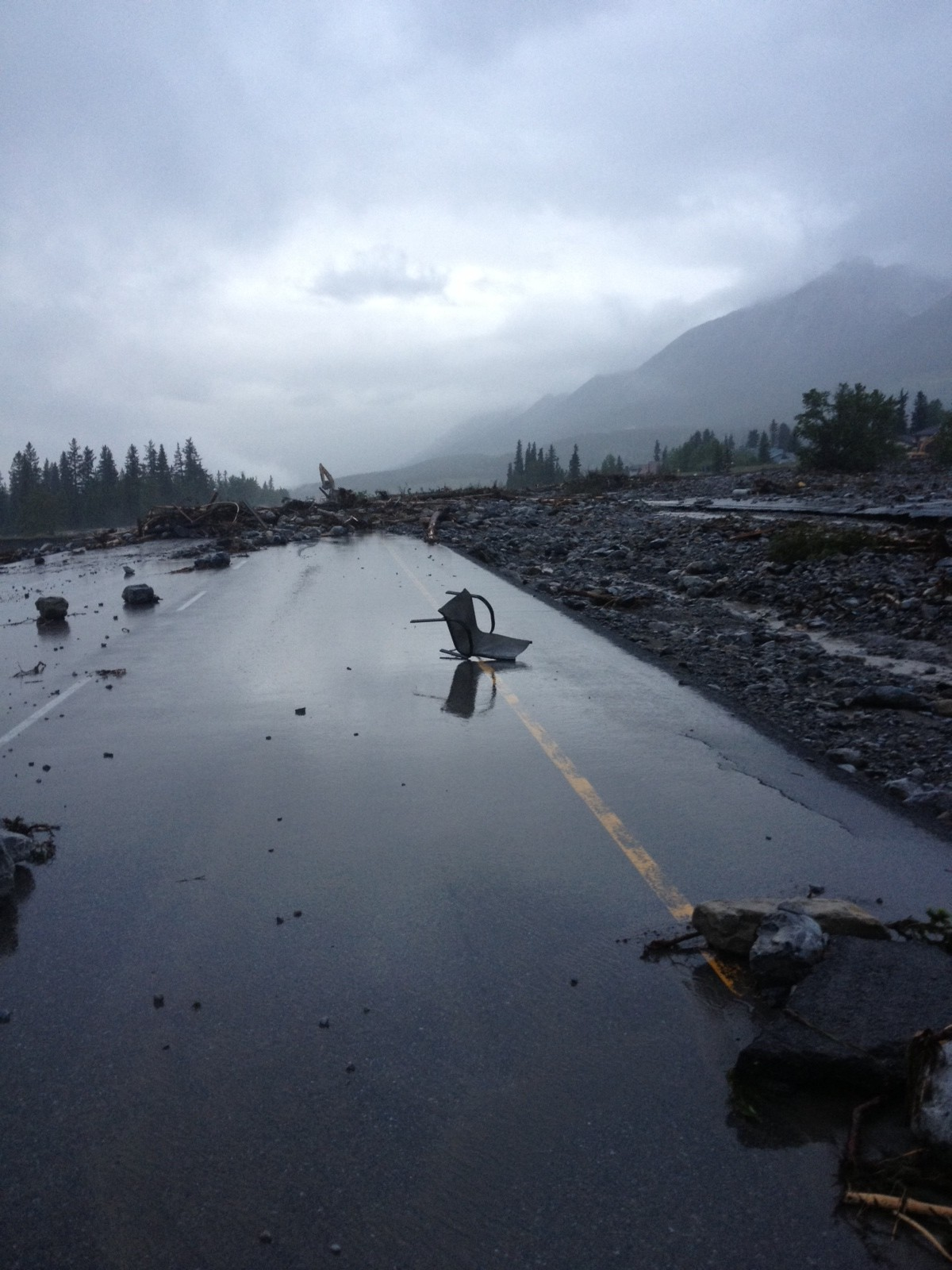 Flooding debris littering and closing the Trans Canada Highway in Canmore, Alberta